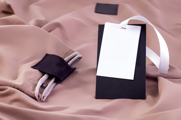 Macro mock up fabric empty black patch for the brand logo on the sleeve and a paper label on a white ribbon on beige clothing