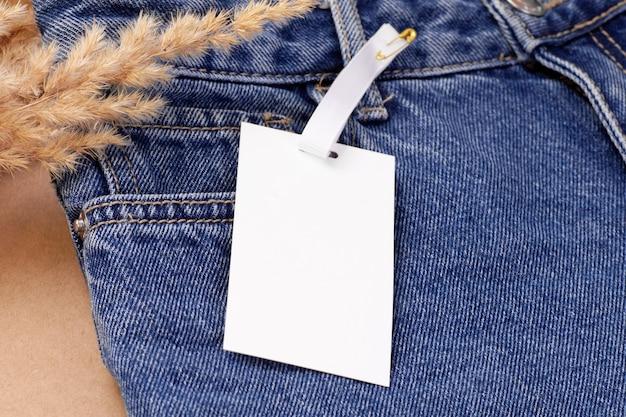 매크로는 마른 팜파스 잔디 또는 갈대 장식으로 청바지에 로고 핀에 흰색 빈 종이 태그 또는 레이블을 조롱합니다.