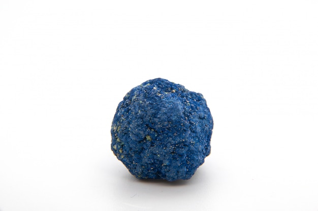 Macro of natural mineral rock specimen of raw azurite stone isolated on a white background. ore azurite semiprecious geological crystal.