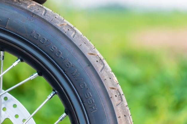앞 오토바이 고무 바퀴의 매크로 번호 코드. 복사 공간이있는 도로에서 야외 촬영