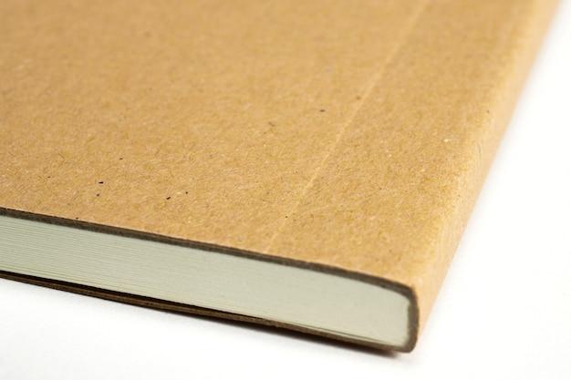 白で隔離される段ボールのハードカバーと空白のノートブックコーナーのマクロ