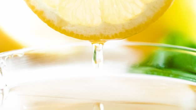 カットレモンスライスから落ちる蜂蜜の液滴のマクロ。