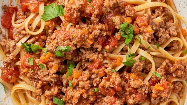 Macro pasta bolognese linguine with mincemeat and tomatoes, close up, long width banner, top view