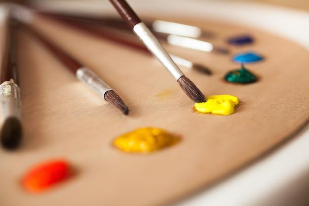 Макро фотография кисти, смоченной желтой масляной краской с поддона