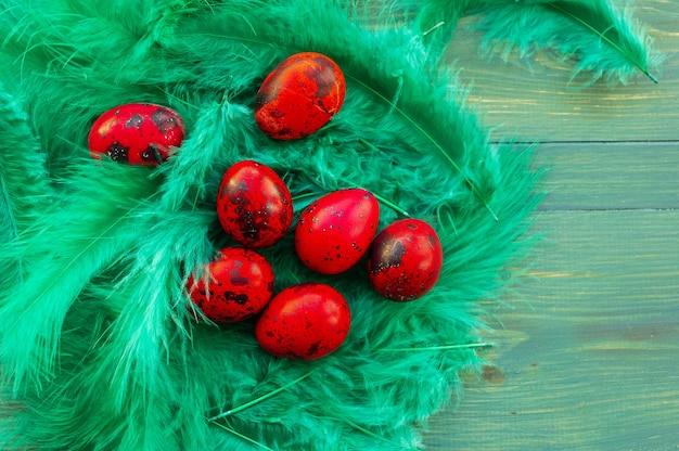 赤いイースターウズラの卵のマクロ写真。緑の木の背景に赤いウズラの卵を描いた。伝統的な