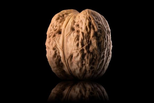 Макро-фотография всего грецкого ореха с отражением, изолированным на черном фоне с обтравочным контуром.