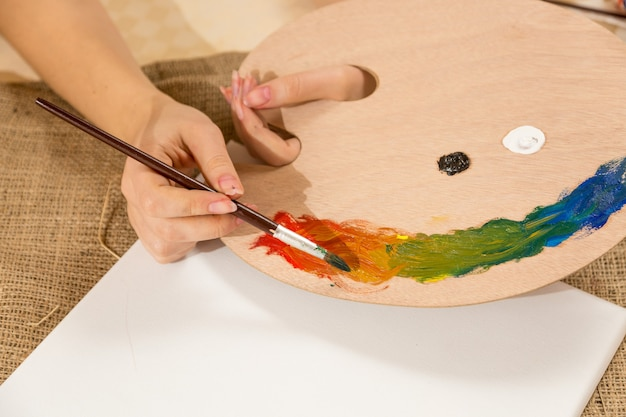 Макро фотография молодой художницы, окунающей кисть в краску на поддоне