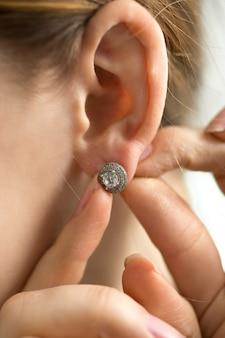 Макро фотография молодой женщины, примеряющей бриллиантовую серьгу