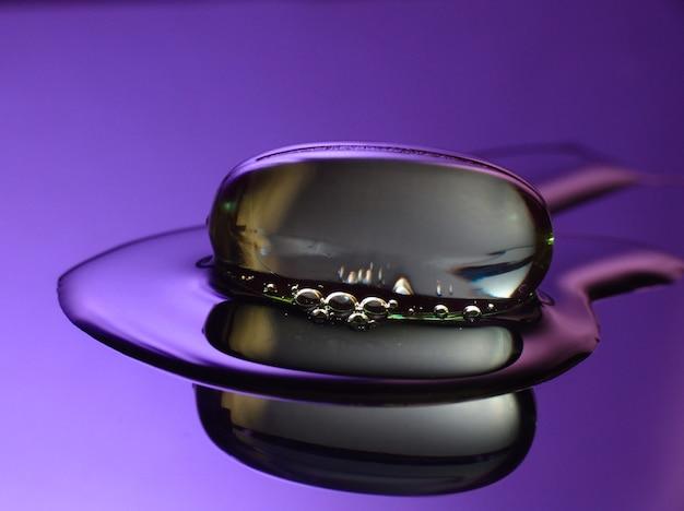 反射性液体上の透明な薬用カプセルのマクロ写真。紫の色