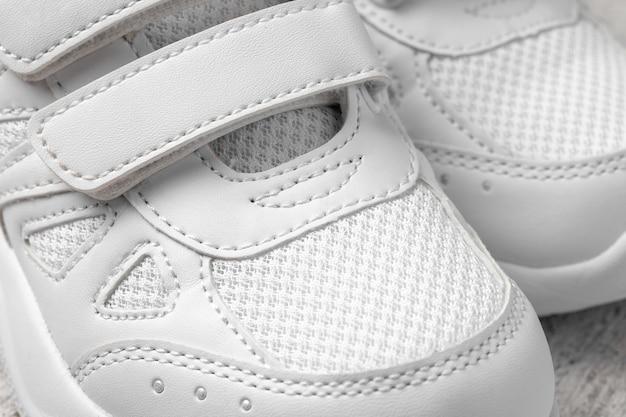 흰색 운동화의 매크로 사진 2개의 흰색 어린이 신발에 벨크로 패스너가 있어 편리합니다.