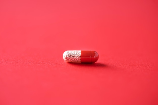Macro of red capsules on red background. copy space. bunch of drugs, cold flu treatment.