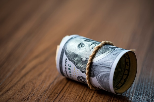 Macro of roll of 100 us dollar banknote on wooden background and copy space