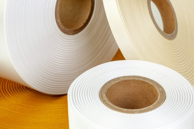 Macro set of four coils of silk ribbons in white beige orange colors of different sizes for labels or branding isolated