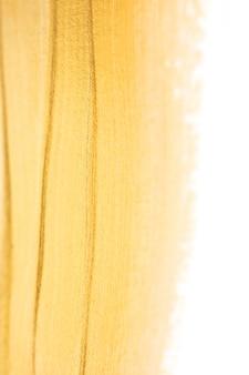 選択的な焦点で白い背景に分離されたマクロ光沢のある金色のペイントテクスチャ。パーティーや結婚式の招待状のためのキラキラゴールドグローエレガントな滑らかなテンプレート