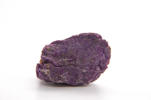 Макросъемка образца натурального минерального камня - необработанного стихтитового камня на темном гранитном фоне с алтая, россия