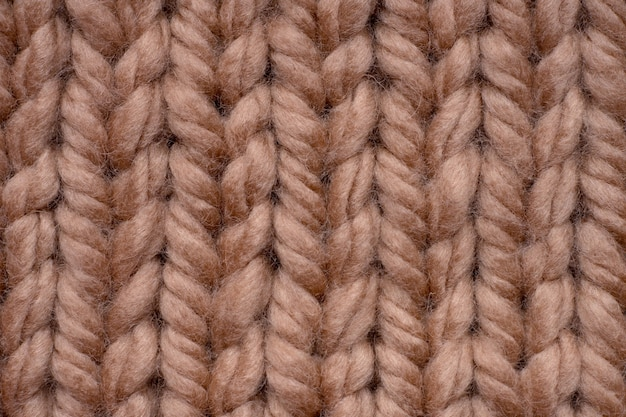 Macro shot of brown woolen knitted fabric texture.