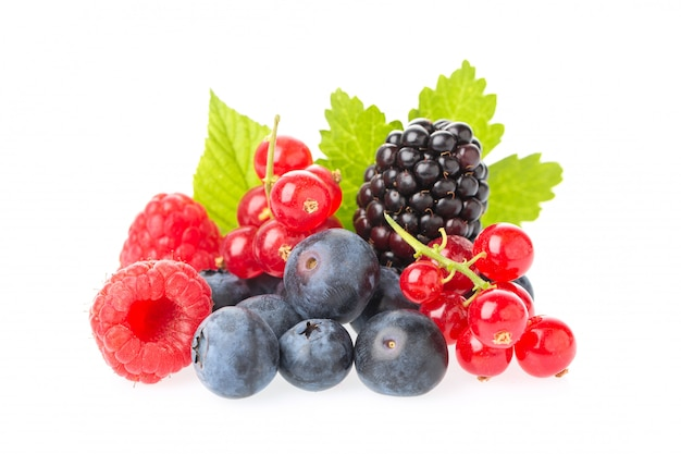 Macro shot of fresh raspberries, blueberries, blackberries, red currant and blackberry with leaves isolated on white background.