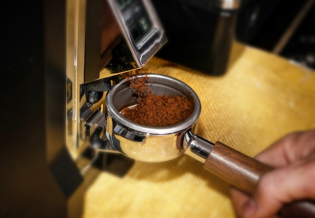 Macro shot grinding coffee on professional grinder machine