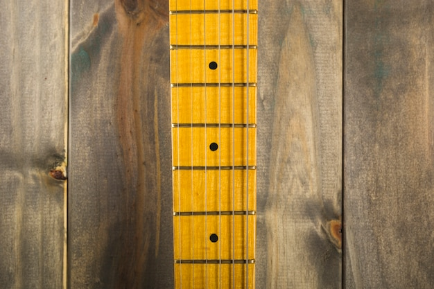 Macro shot of guitar strings and fret board on wooden background