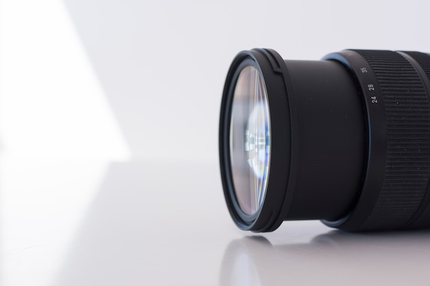 Macro shot of modern digital camera lens over white background