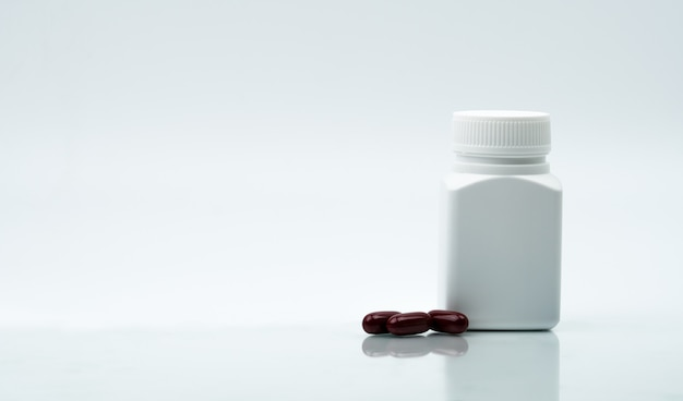 Macro shot of multivitamins capsule pills and closed plastic bottle with blank label and copy space