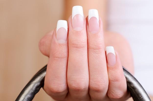 フランスのマニキュアと美しいエレガントな女性の指のマクロ撮影