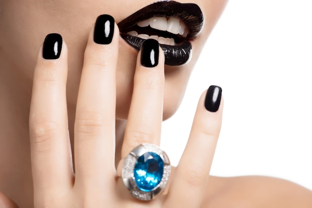여자의 입술과 손톱의 매크로 촬영은 밝은 색상의 검은 색으로 칠해졌습니다.