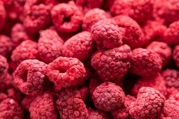 フリーズドライした有機ラズベリー、生のおいしいスナック、調理用ベーキング材料のマクロ撮影。赤い果実のジューシーな夏の背景。天然糖、健康食品、新鮮な果物のコンセプト、テキストスペース