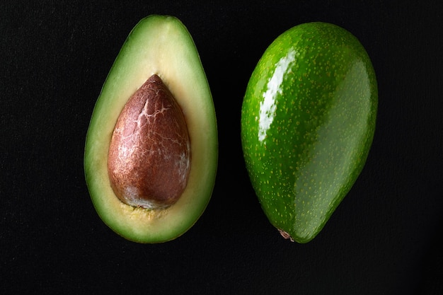 Макросъемка свежих авокадо, разрезанных пополам на черном фоне