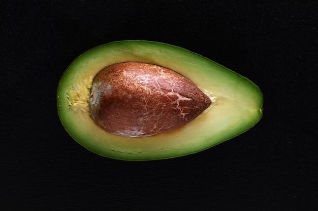 Макросъемка свежих авокадо, разрезанных пополам на черной поверхности