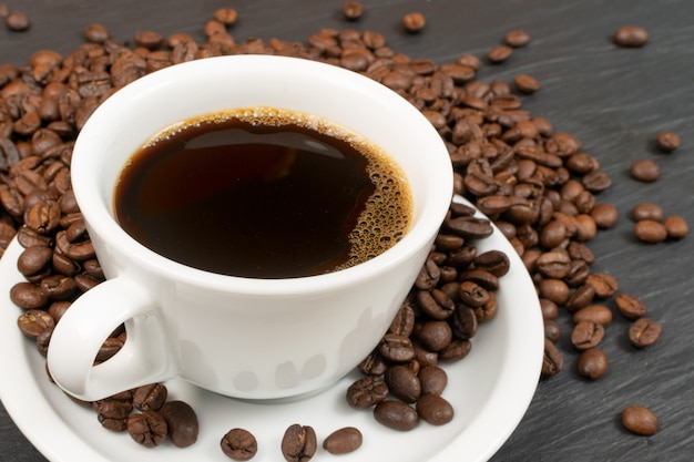 黒い石の背景に熱いエスプレッソカップとコーヒー豆のマクロ撮影。