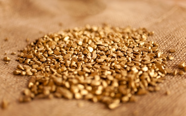 Макросъемка холма золотых самородков, лежащих на мешковине