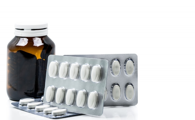 Макросъемка капсулы витаминов в янтарной стеклянной бутылке с пустой этикеткой и таблетками в блистерной упаковке