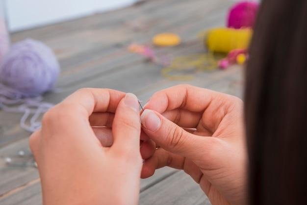 針にウールを挿入する女性のマクロ撮影