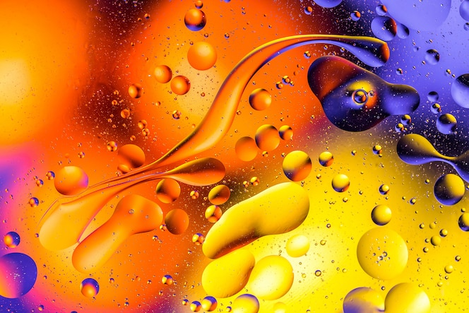 Macro shot of oil bubbles with water on colorful background.