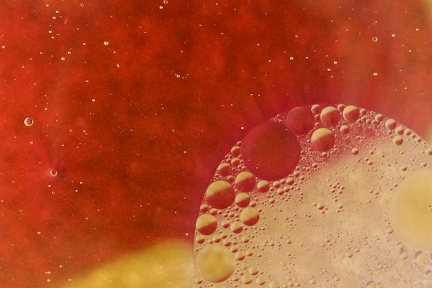Macro shot of oil drops on red colored background
