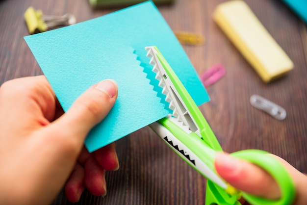 Macro shot of a person's hand cutting turquoise paper with zigzag scissor