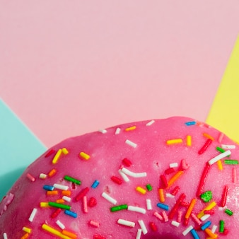 Macro shot of pink donut with colorful sprinkles on colored backdrop
