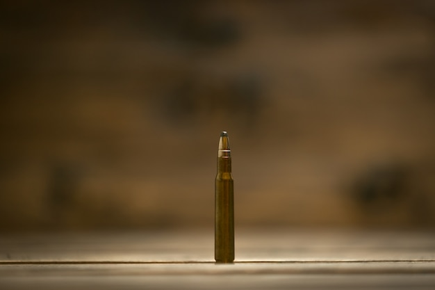 Macro shot of riffle bullet against dark wooden table
