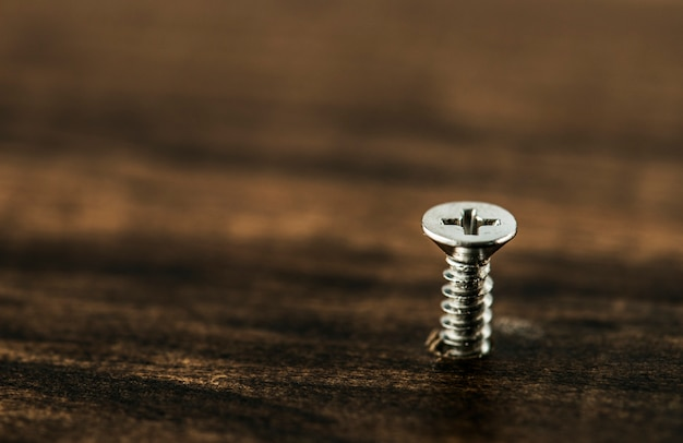 Macro shot of screw on wooden background