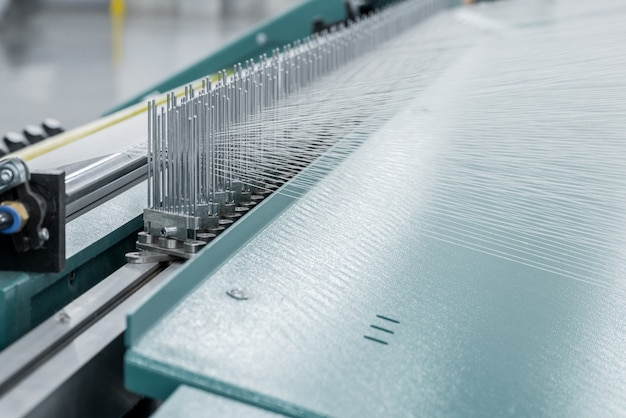 Macro shot of a stretched thread. machinery and equipment in a textile factory