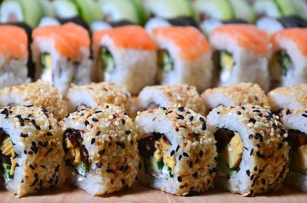 A macro shot of a sushi set of many rolls is located on a wooden cutting board on a table in the kitchen of a sushi bar.