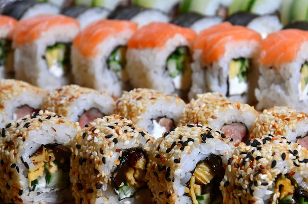 A macro shot of a sushi set of many rolls is located on a wooden cutting board