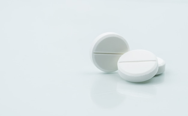 Macro shot of three white chewable tablets on white background with shadows.