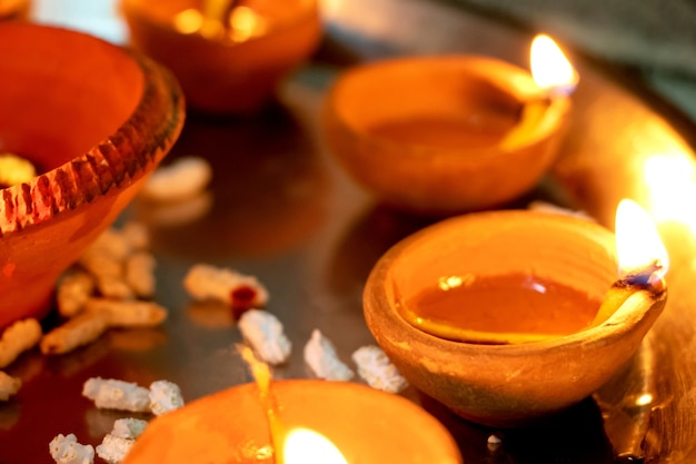 Macro shots of diyas being lit by hand or candle for the hindu religious festival of diwali. these colorful earthern pots hold oil and a cotton wick to light