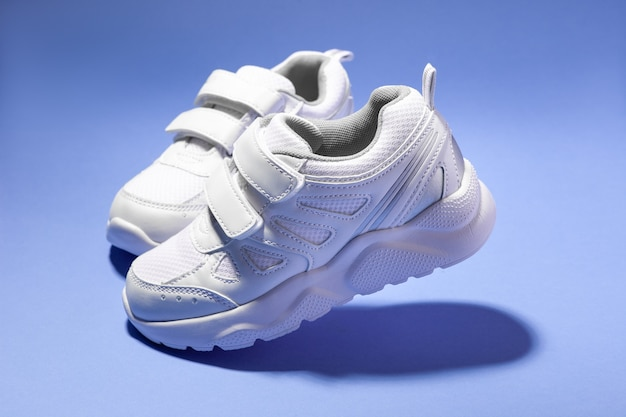 Macro side view two flying white kid running shoes with velcro isolated on purple background