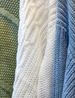 Macro texture of three sweaters. fabric fiber green, white and blue background.