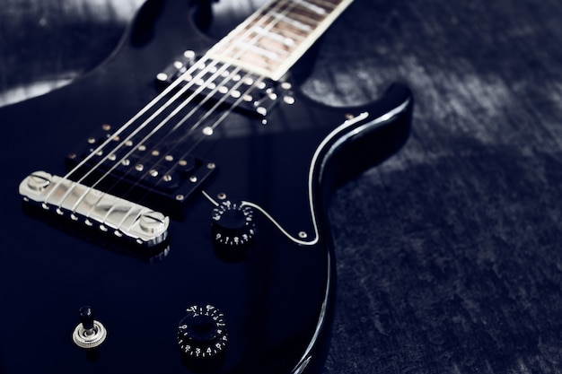 Macro view of the black electric guitar, selective focus on the signal regulator handle, with copy space, low depth of sharpness