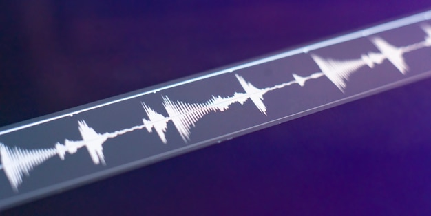 A macro view of the computer monitor screen with sound audio wave graph volume