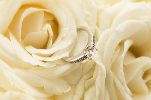 白いバラの上に横たわっているダイヤモンドと美しい金の指輪のマクロビュー